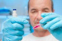 El científico sostiene un tubo de prueba con una muestra Foto de archivo libre de regalías