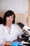El científico trabaja con el microscopio Imagen de archivo libre de regalías