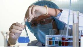 El científico vierte las sustancias químicas de un tubo de ensayo en un frasco, accionando una reacción química intensa almacen de video