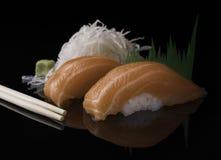 El cierre de color salmón fresco del sushi para arriba sirvió en una superficie reflexiva negra Fotos de archivo libres de regalías