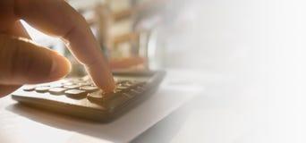 El cierre de la mano humana está consumiendo la calculadora imagenes de archivo