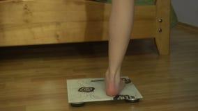 El cierre de la mujer joven se levanta en la escala para pesar almacen de metraje de vídeo