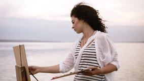 El cierre de una mujer magnífica con el pelo rizado moreno se está levantando en frente el lago y está dibujando usando una palet almacen de metraje de vídeo