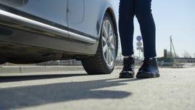 El cierre del ángulo bajo encima del tiro de las piernas de los pies de la chica joven sale de día soleado del coche y del baile  almacen de metraje de vídeo