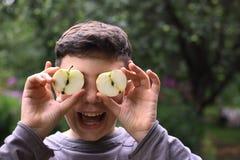 El cierre del muchacho del adolescente encima del retrato con la manzana cortada observa Fotos de archivo libres de regalías