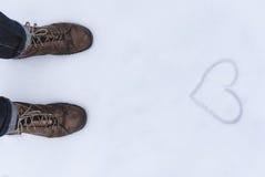 El cierre del zapato de los hombres encima de la visión con simbol del amor wrtien en la nieve Fotografía de archivo