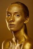 El cierre encima de chispas de oro de la piel de la mujer hermosa del retrato brilla Foto de archivo