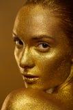 El cierre encima de chispas de oro de la piel de la mujer hermosa del retrato brilla Fotografía de archivo libre de regalías