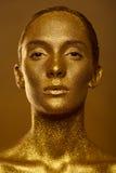 El cierre encima de chispas de oro de la piel de la mujer hermosa del retrato brilla Imagen de archivo