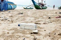 El cierre encima de la botella plástica usada vacía y de otra basura rechazada en la playa del mar en fondo es barcos de pesca Fotos de archivo libres de regalías