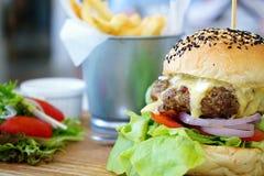 El cierre encima de la hamburguesa jugosa de la carne de vaca de A con el queso derretido servido con la ensalada y las patatas f Imágenes de archivo libres de regalías