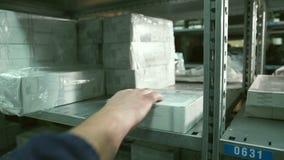 El cierre encima de la mano del hombre toma la caja del estante dentro del almacén almacen de metraje de vídeo