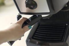 El cierre encima de la mano la mujer está preparando el café Foto de archivo libre de regalías