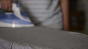 El cierre encima de la mano de la mujer está planchando la ropa en el tablero en la casa almacen de video