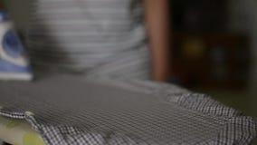 El cierre encima de la mano de la mujer está planchando la ropa en el tablero en la casa metrajes