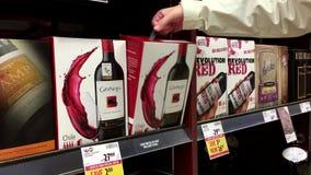 El cierre encima de la mano toma a negro de Guto el vino rojo del estante almacen de metraje de vídeo
