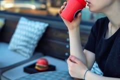 El cierre encima de la mujer joven bebe el café de la taza de papel Imagen de archivo libre de regalías