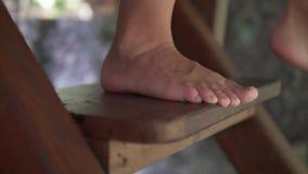 El cierre encima de la opinión de cámara lenta de los pies desnudos de la mujer en las escaleras de madera, piernas descalzas, mu metrajes