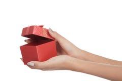 El cierre encima de las manos abre una caja de regalo roja Fotografía de archivo