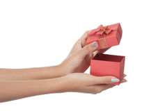 El cierre encima de las manos abre una caja de regalo roja Fotos de archivo libres de regalías
