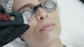El cierre encima de las manos del cosmetólogo hace laser retiro vascular en la cara de la mujer con el equipo especial almacen de metraje de vídeo