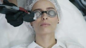 El cierre encima de las manos del cosmetólogo hace laser retiro vascular en la cara de la mujer con el equipo especial almacen de video