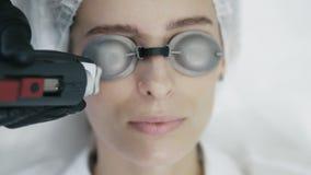 El cierre encima de las manos del cosmetologist con el equipo especial hace el procedimiento del laser para el retiro de los vaso almacen de metraje de vídeo
