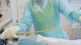 El cierre encima de las manos de la enfermera desinfecta el dispositivo del ultrasonido durante la operación sclerotherapy metrajes