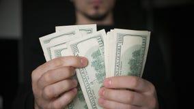 El cierre encima de las manos masculinas cuenta cientos billetes de d?lar en la oscuridad almacen de video