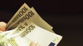 El cierre encima de las manos masculinas cuenta a Euros Banknotes metrajes