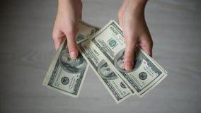 El cierre encima de las manos masculinas del FE cuenta cientos billetes de d?lar en el fondo gris metrajes