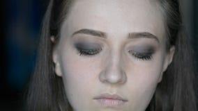 El cierre encima del artista de maquillaje que pone en maquillaje en el ` modelo s observa y las frentes con imagen del cosmeticm almacen de video