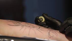 El cierre encima del artista del tatuaje demuestra el proceso de hacer el tatuaje que consigue con la pintura Guantes estéril Amo metrajes