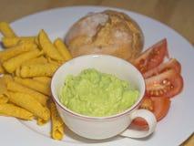 El cierre encima del guacamole con la tortilla de maíz rueda los tomates tajados y foto de archivo