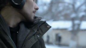 El cierre encima del hombre barbudo de pelo largo joven del retrato en una chaqueta y auriculares grandes se sienta en transporte almacen de metraje de vídeo