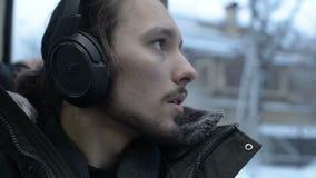 El cierre encima del hombre barbudo de pelo largo joven del retrato en una chaqueta y auriculares grandes se sienta en transporte almacen de video