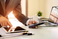 El cierre encima del hombre de negocios calcula datos de las finanzas en la tableta a fotos de archivo libres de regalías