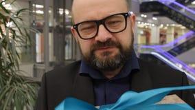 El cierre encima del hombre en una chaqueta da un regalo a la cámara y a la sonrisa interiores en una tienda almacen de video