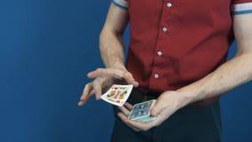 El cierre encima del ilusionista en camisa roja realiza trucos mágicos de los naipes