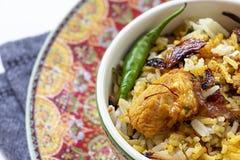 El cierre encima del pollo indio Halal Biryani sirvió con raita del tomate del yogur sobre foco selectivo del fondo blanco fotos de archivo libres de regalías