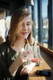 El cierre encima del retrato de la muchacha adolescente hermosa sonriente del estudiante con una taza de cristal bebe a través de Fotos de archivo libres de regalías