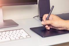 El cierre encima del varón de las manos que trabaja en la tableta gráfica Imagenes de archivo