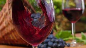 El cierre encima del vino rojo se vierte en un vidrio metrajes
