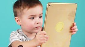 El cierre encima niño lindo de la cara del pequeño utiliza una tableta que se sienta en la tabla, aislada en azul almacen de video