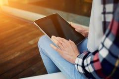 El cierre hasta las manos de la mujer joven de la visión sostiene la tableta negra con la pantalla vacía en blanco Imagenes de archivo