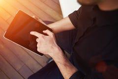 El cierre hasta las manos del hombre joven de la visión sostiene la tableta negra con la pantalla vacía en blanco Foto de archivo