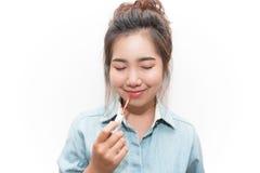 El cierre hermoso de la mujer joven observa y haciendo maquillaje usando un labio Imagen de archivo
