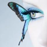 El cierre hermoso del ojo de la mujer para arriba con la mariposa se va volando Imágenes de archivo libres de regalías