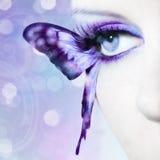 El cierre hermoso del ojo de la mujer para arriba con la mariposa se va volando Foto de archivo libre de regalías