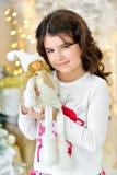 El cierre hermoso encima del portraite de la muchacha rizada con las luces de las guirnaldas de la Navidad del oro y las decoraci Imagen de archivo